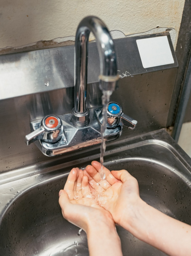 Hands being washed at a mixer tap.