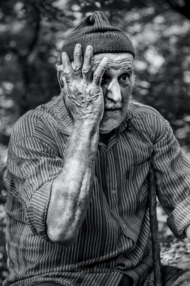 An elderly gentleman holding the right side of his face.