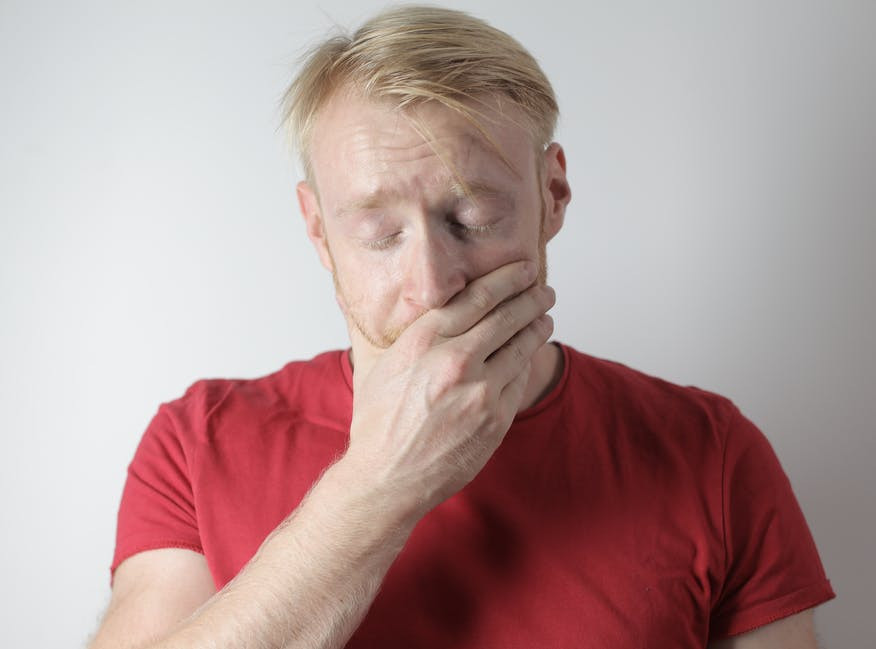 A distressed and weary man covering his mouth with his hand while suffering from hiccups