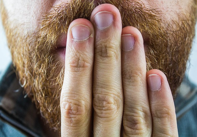 A mouth of a bearded man covered with the hand due to the occurrence of hiccups.