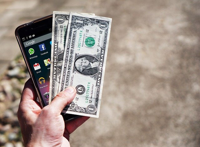 Picture of a hand holding a mobile phone and a few $1 bills. This illustrates that diclofenac can be afforded by many people, especially cash-paying, ordinary people without medical aid.